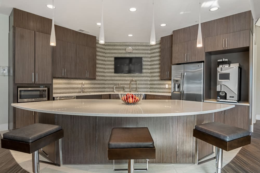 Modern style community kitchen with adjustable counter stools at Marq at Crabtree in Raleigh, North Carolina