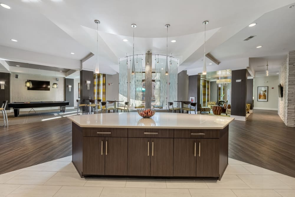 Modern and sleek community clubhouse with kitchen, seating, and dining areas at Marq at Crabtree in Raleigh, North Carolina