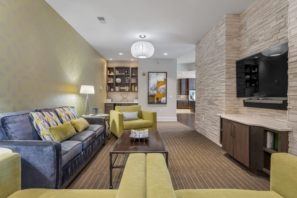 Semi private sitting area with couch, cushioned chairs, and television entertainment area at Marq at Crabtree in Raleigh, North Carolina