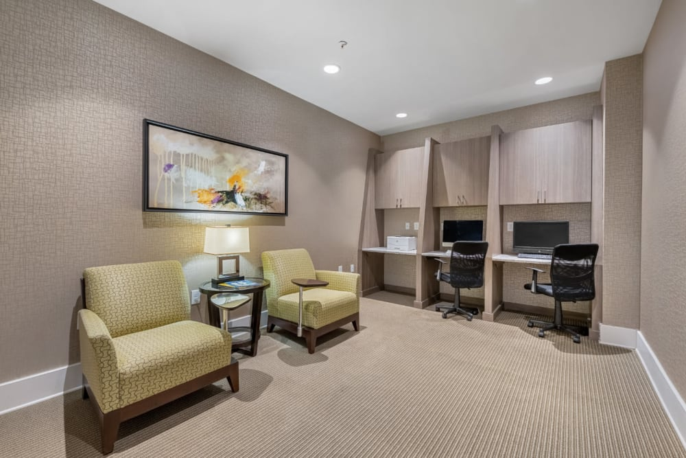 Business workstations with printer and cushioned desk chairs nearby at Marq at Crabtree in Raleigh, North Carolina