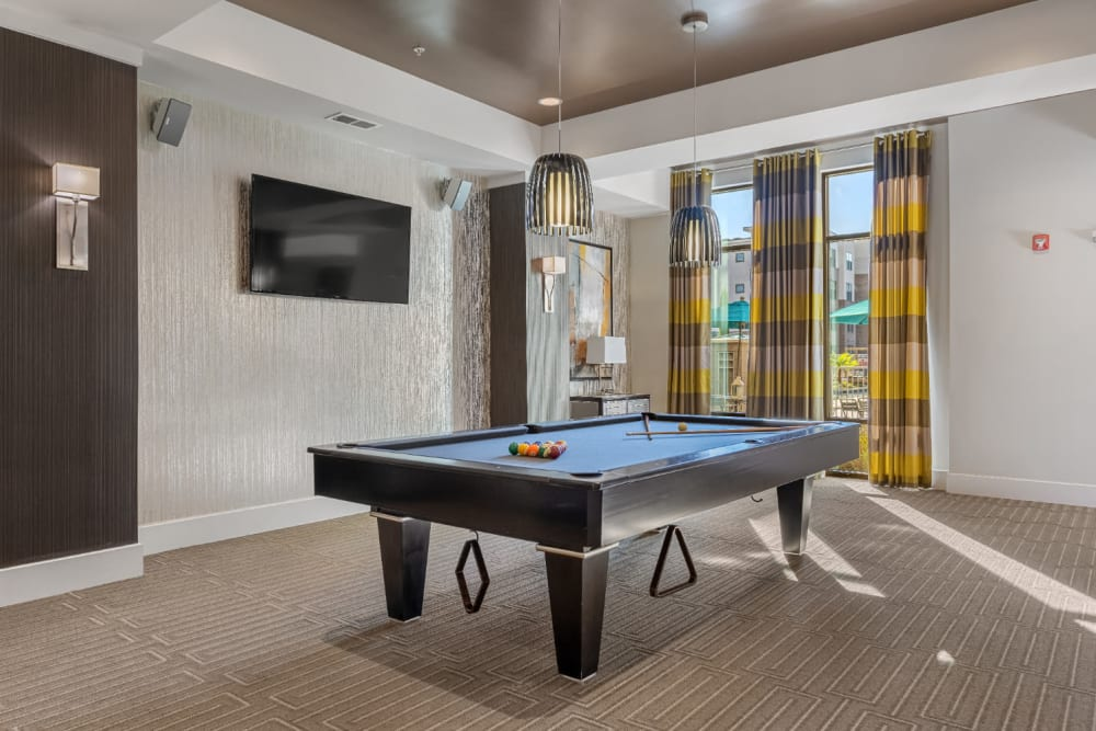 Pool table area with wall mounted television and speakers at Marq at Crabtree in Raleigh, North Carolina
