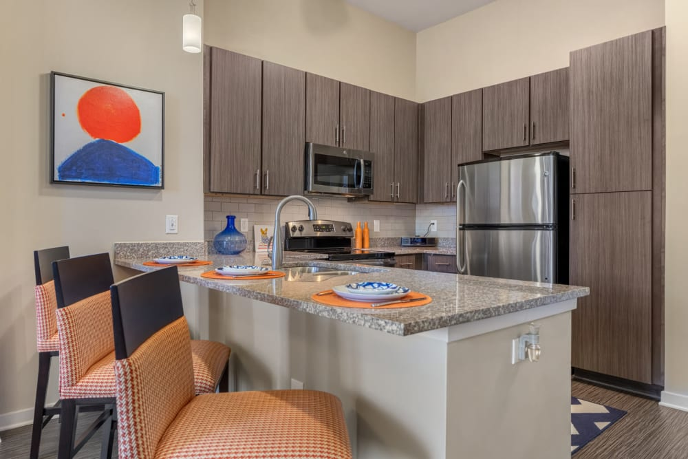 Bright kitchen with counter stool chairs and granite countertops at Marq at Crabtree in Raleigh, North Carolina