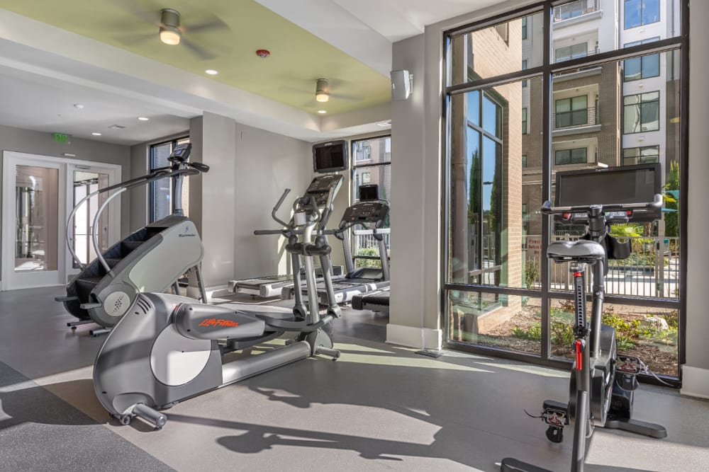 Cardio machines facing large windows in fitness room at Marq at Crabtree in Raleigh, North Carolina