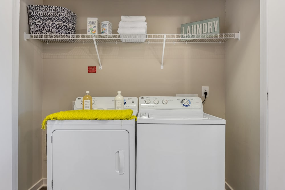 Laundry nook with full size washer and dryer and wired shelving at Marq at Crabtree in Raleigh, North Carolina