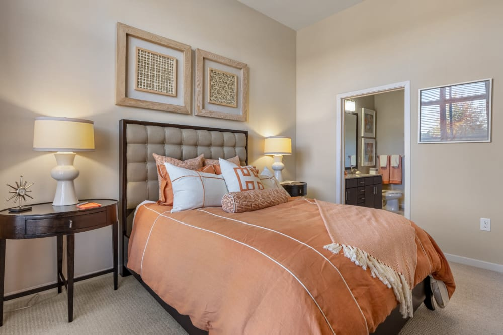 Bright and cozy bedroom with large bed, side tables, and private bathroom at Marq at Crabtree in Raleigh, North Carolina