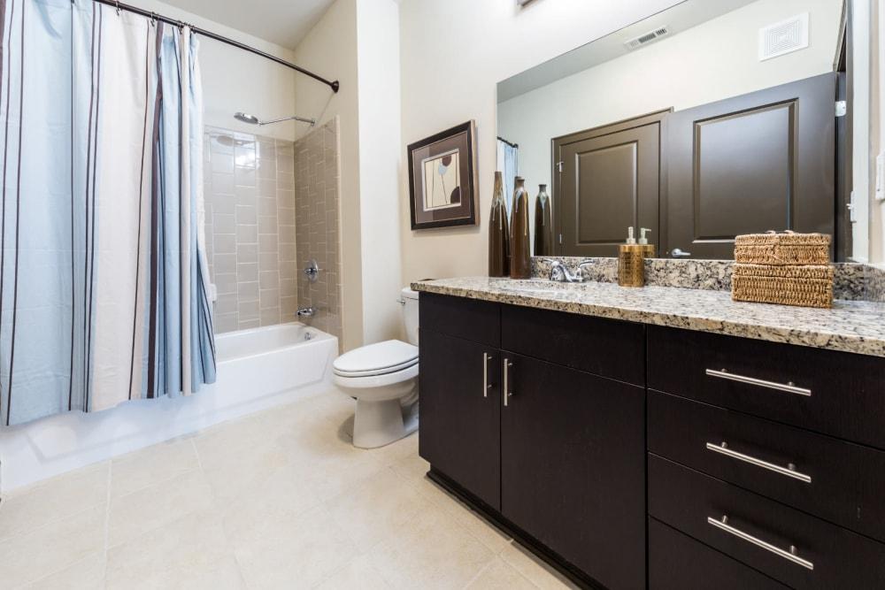 Spacious bathroom with bathtub, granite countertop, and tiled floor at Marq Eight in Atlanta, Georgia
