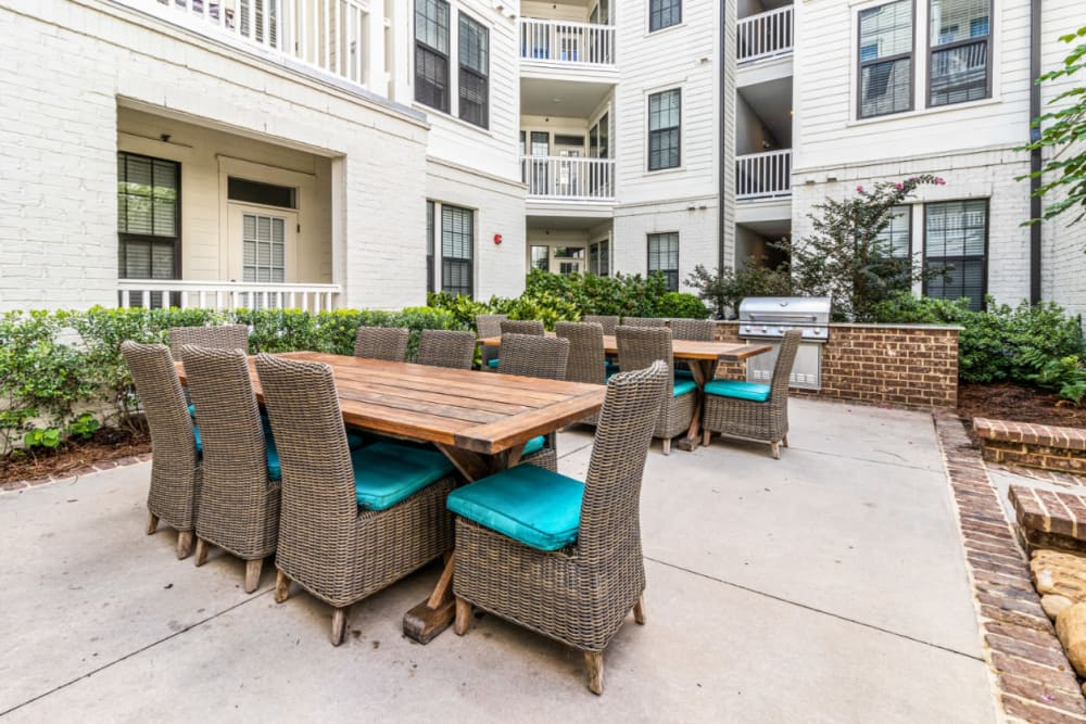 Outdoor BBQ area with large dining tables and chairs at Marquis at Buckhead in Atlanta, Georgia