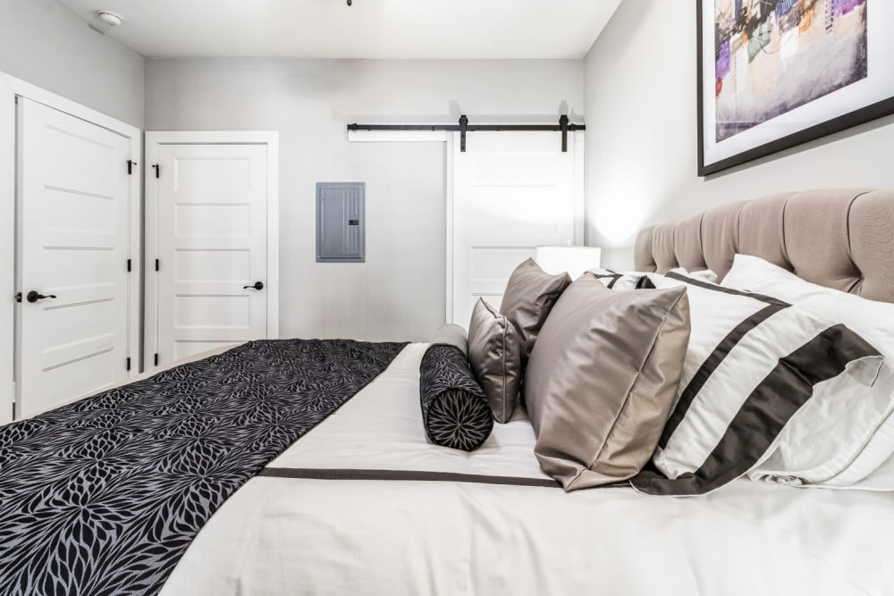 Bright bedroom with large bed and farmhouse door on rail at Marquis at Buckhead in Atlanta, Georgia