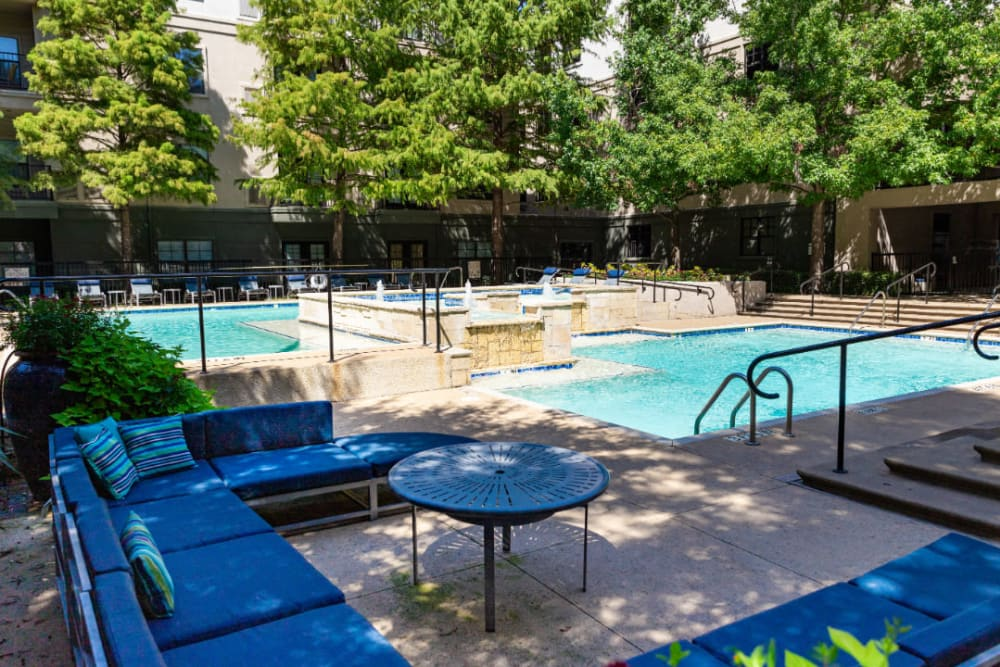 Lounge couches next to sparkling pool at Marquis at Texas Street in Dallas, Texas