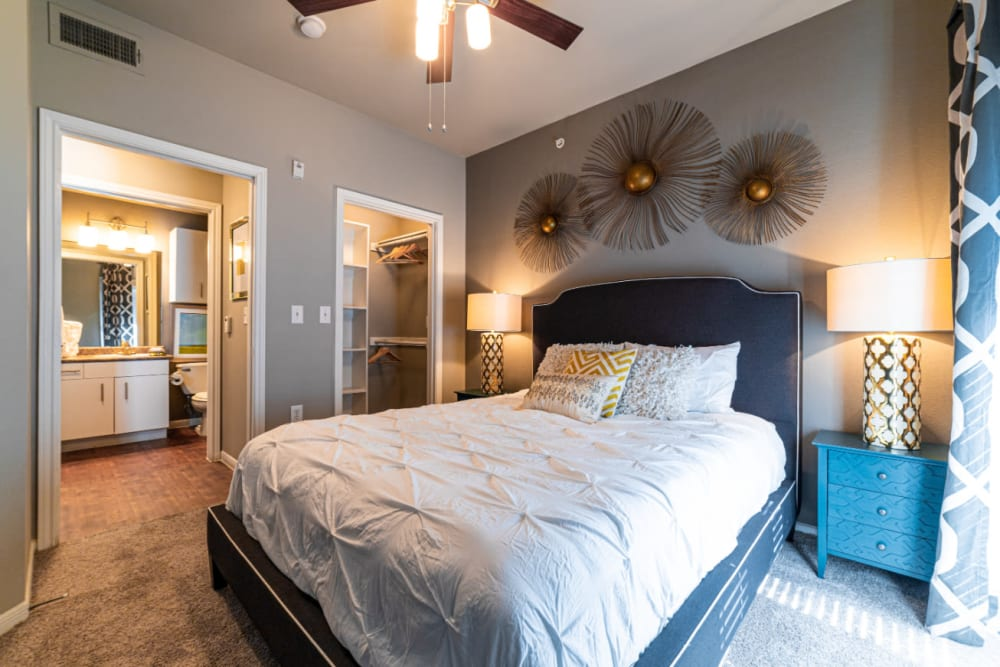 Carpeted bedroom with full size bed and modern style furniture, walk-in closet, and private bathroom at Marquis at Texas Street in Dallas, Texas