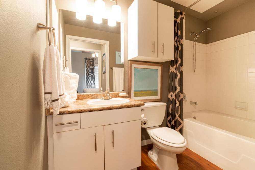 Bright bathroom with bathtub and wood flooring at Marquis at Texas Street in Dallas, Texas