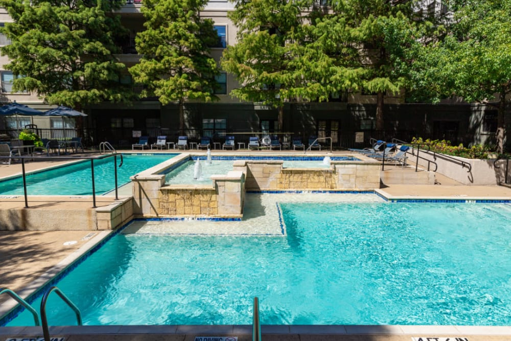 Water feature in center of sparkling pool with lounge chairs in back at Marquis at Texas Street in Dallas, Texas