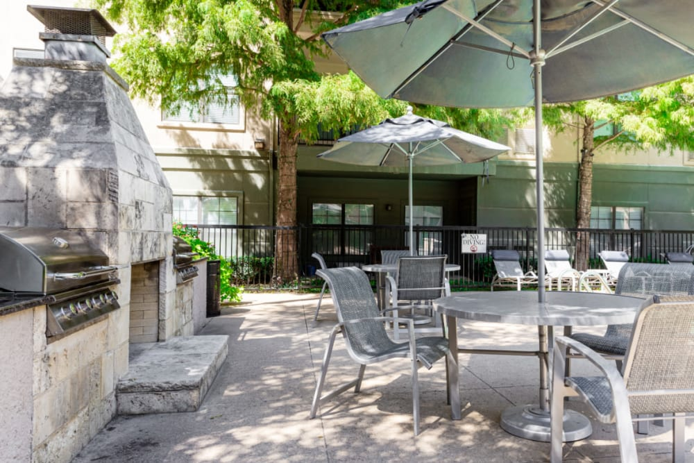Outdoor stainless steel BBQ, fireplace, and dining tables and chairs at Marquis at Texas Street in Dallas, Texas