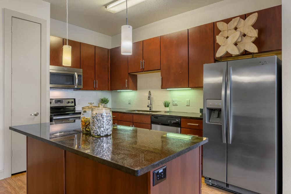 Modern style kitchen with granite countertops and stainless steel appliances at Sabina in Austin, Texas