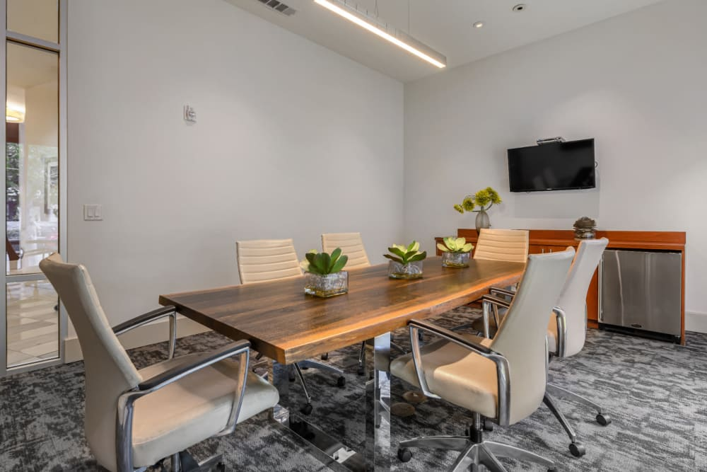 Executive business meeting room with small fridge and wall mounted monitor of Sabina in Austin, Texas