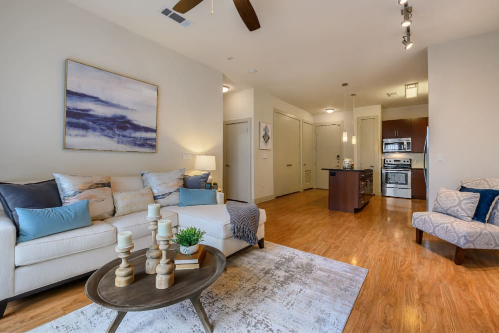 Open living space with modular couch, sitting chair, and coffee table leading into kitchen at Sabina in Austin, Texas