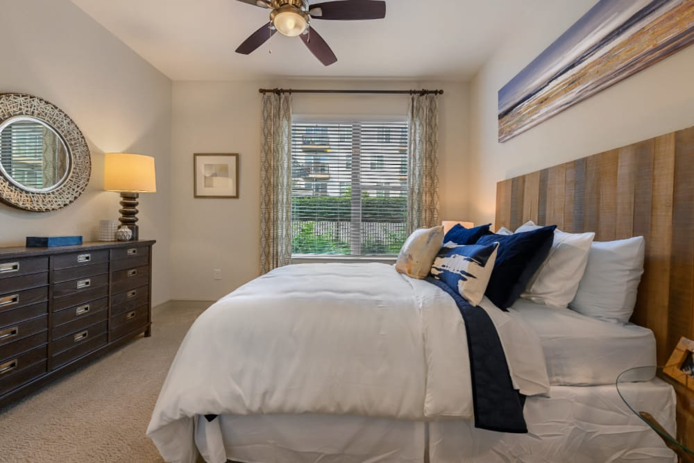 Carpeted bedroom with dresser, wood headboard, and window at Sabina in Austin, Texas