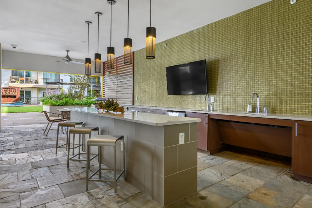 Semi indoor community kitchen with granite counter and counter stools at Sabina in Austin, Texas