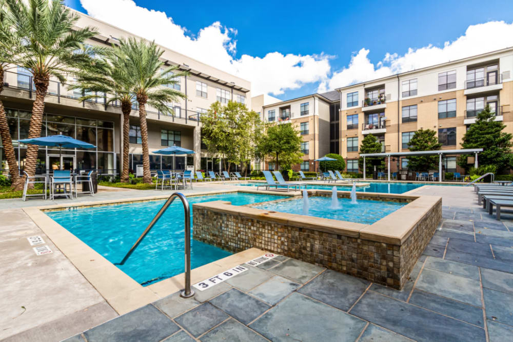 Pool deck with water feature and lounge chairs at The Marq on Voss in Houston, Texas