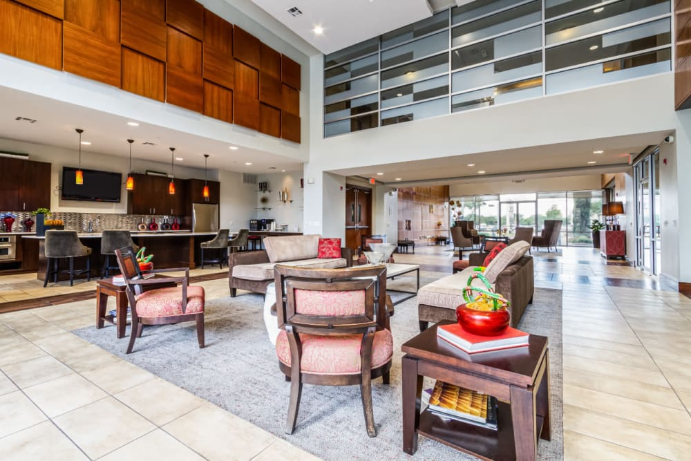 Community clubhouse seating area with kitchen in background at The Marq on Voss in Houston, Texas