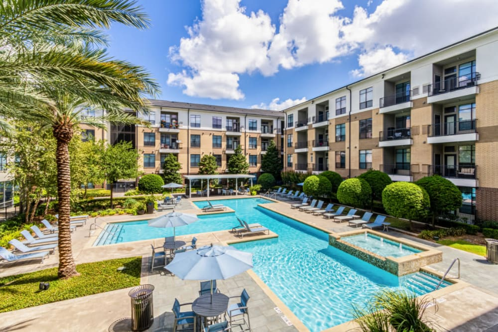 Sparkling resort style pool surrounded by building units at The Marq on Voss in Houston, Texas
