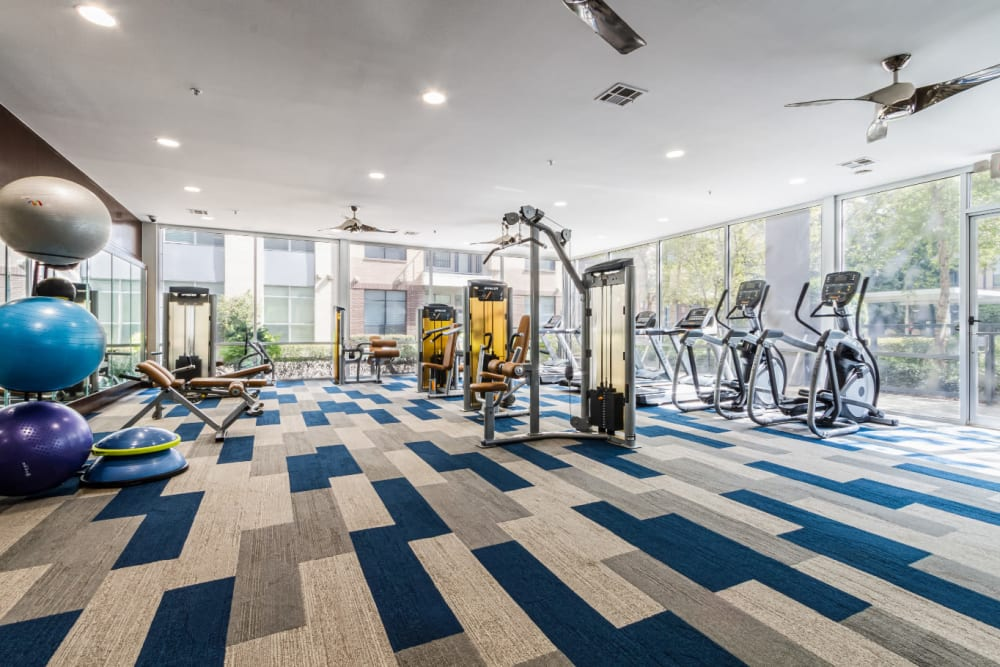 Large fitness room with medicine balls, cardio machines, and assisted weight machines at The Marq on Voss in Houston, Texas