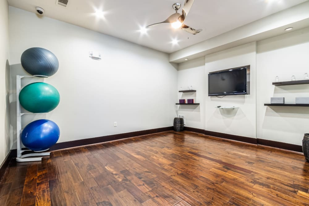 Private exercise room with medicine balls and wall mounted monitor at The Marq on Voss in Houston, Texas