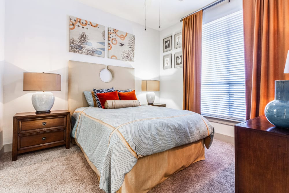 Carpeted bedroom with large bed, modern furniture, and large window at The Marq on Voss in Houston, Texas