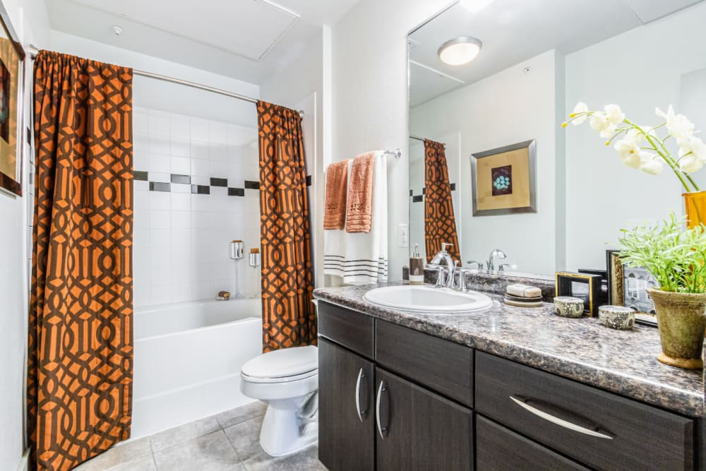 Bright bathroom with tall bathtub and granite counter at The Marq on Voss in Houston, Texas