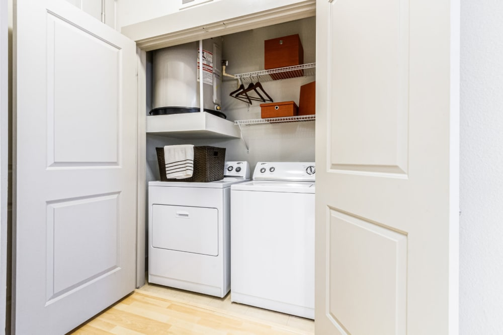 Laundry closet with full size washer and dryer and wired shelves at The Marq on Voss in Houston, Texas