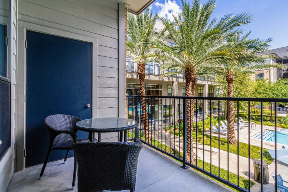 Private balcony with seating area overlooking pool deck at The Marq on Voss in Houston, Texas