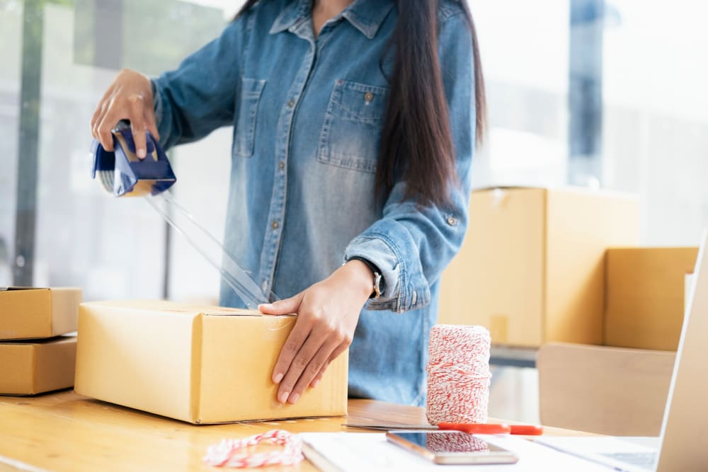 A woman packing boxes near Storage Star Tomball in Tomball, Texas