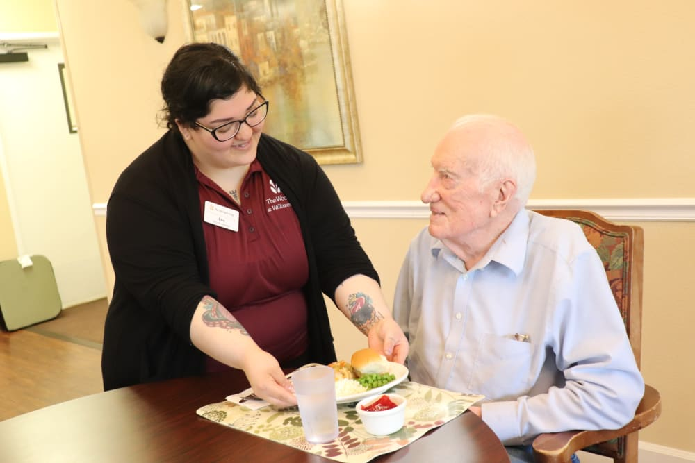 Caregiver with resident enjoying a meal at The Springs at Willowcreek in Salem, Oregon