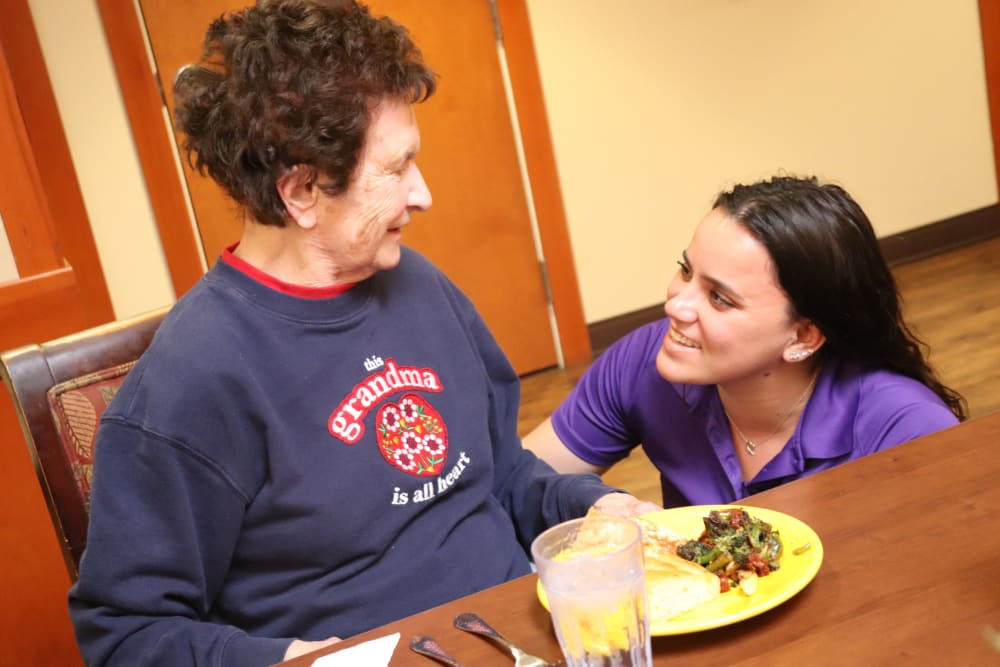 Caregiver and resident smiling at each other over a meal at The Springs at Sherwood in Sherwood, Oregon