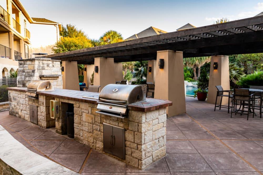 Stainless steel BBQs set in stone with dining section behind at Marquis at Great Hills in Austin, Texas