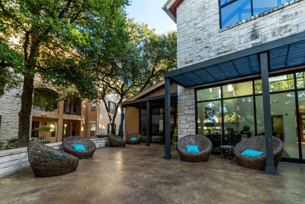 Wicker chairs with cushions in outdoor seating area at Marquis at Great Hills in Austin, Texas