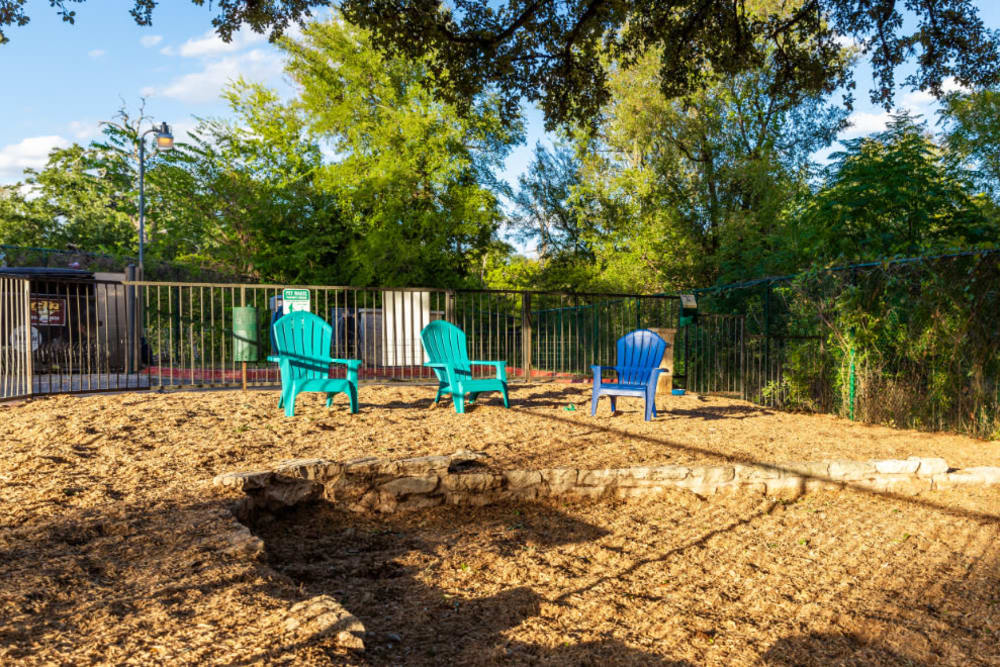 Enclosed dog park area with chairs and dog waste station at Marquis at Great Hills in Austin, Texas