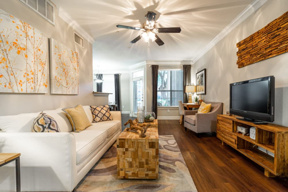 Modern style living room with wood flooring at Marquis at Great Hills in Austin, Texas