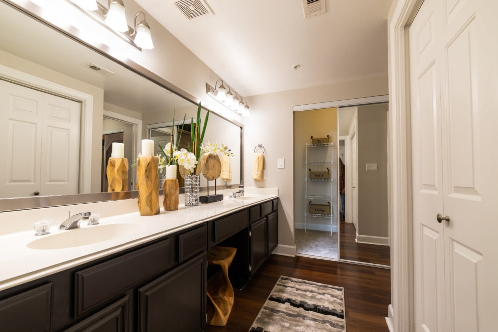 Large bathroom with double sinks, wood flooring, and separate walk-in closet at Marquis at Great Hills in Austin, Texas