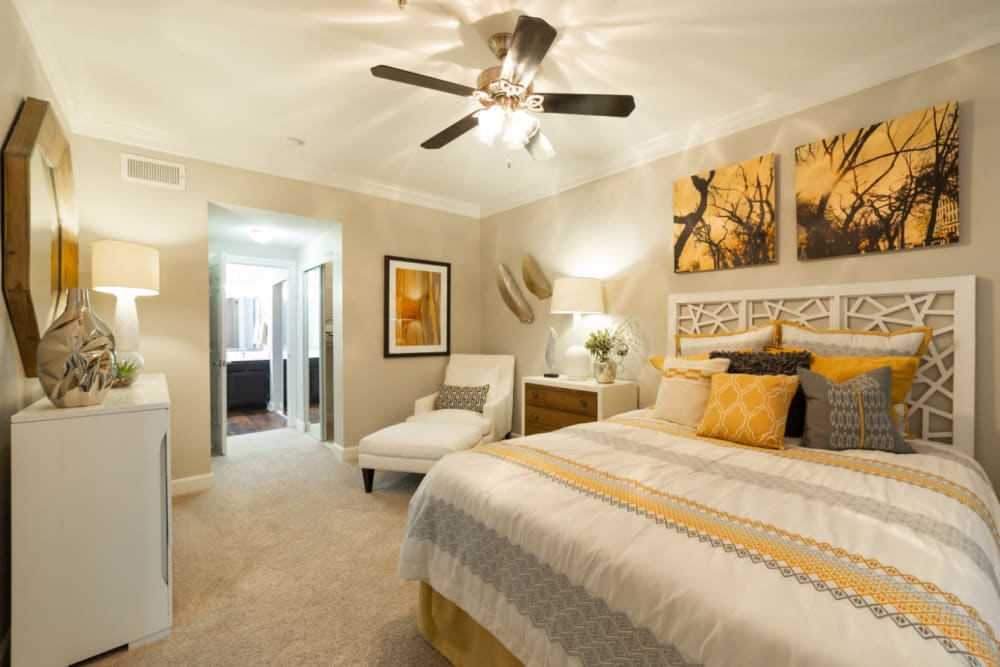 Spacious and bright bedroom with full size bed and sitting area at Marquis at Great Hills in Austin, Texas