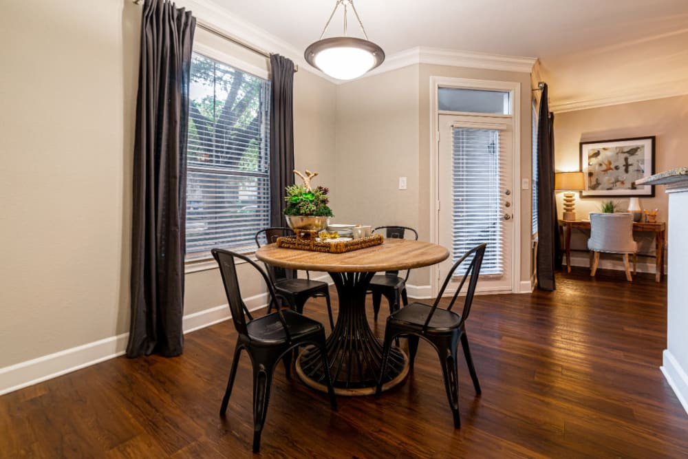 Dining table and chairs with large window and wood flooring at Marquis at Great Hills in Austin, Texas