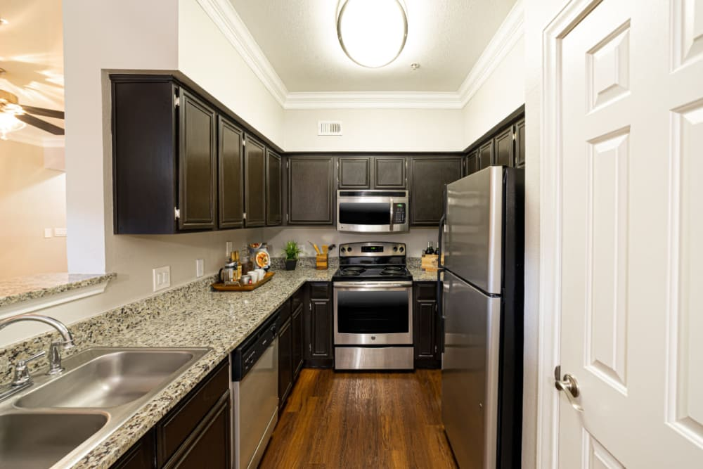 Bright and modern kitchen with stainless steel appliances and granite countertops at Marquis at Great Hills in Austin, Texas