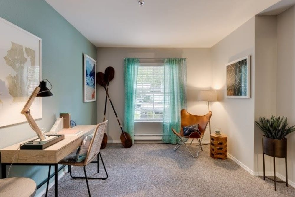 Carpeted bedroom with office desk and sitting chair in corner at Carvel Harbour Pointe in Mukilteo, WA