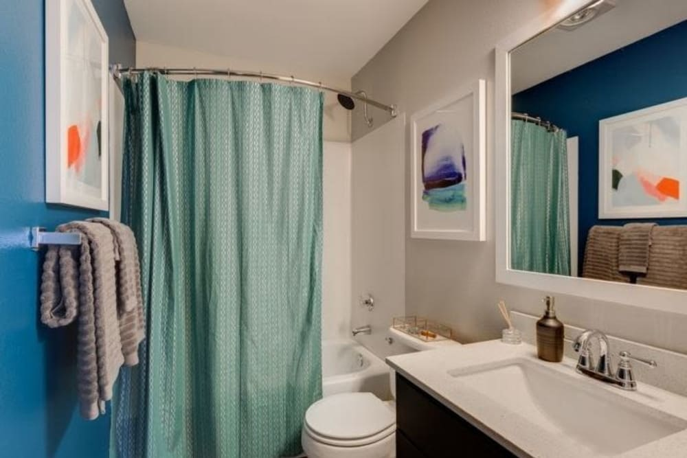Modern and bright bathroom with bathtub and granite counter at Carvel Harbour Pointe in Mukilteo, WA
