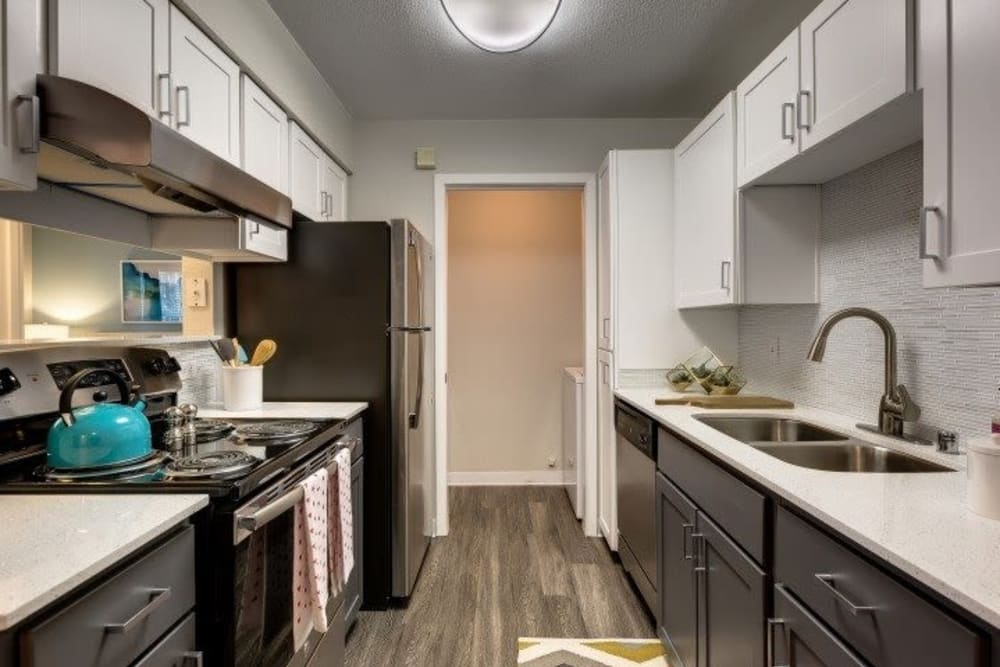 Modern style kitchen with doo flooring and cabinets and white granite countertops at Carvel Harbour Pointe in Mukilteo, WA