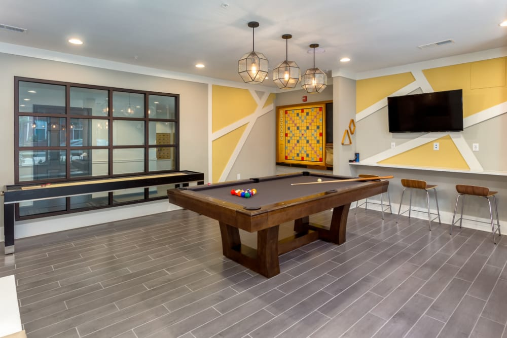 Pool table, shuffleboard, and wall-mounted scrabble in community clubhouse at Marq on Ponce in Atlanta, Georgia