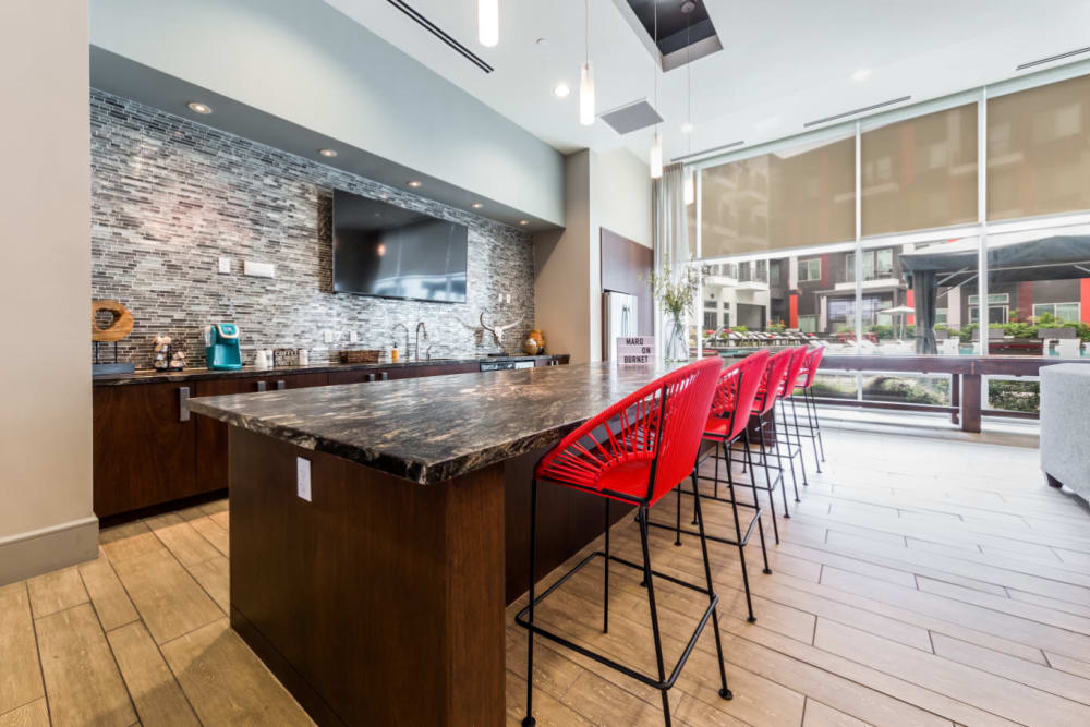 Granite counter with bar stool chairs in community clubhouse kitchen area at Marq on Burnet in Austin, Texas