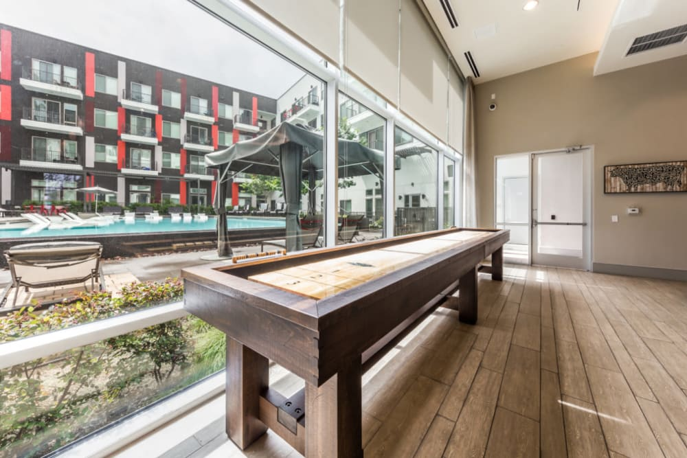 Shuffleboard next to window with view of pool deck at Marq on Burnet in Austin, Texas