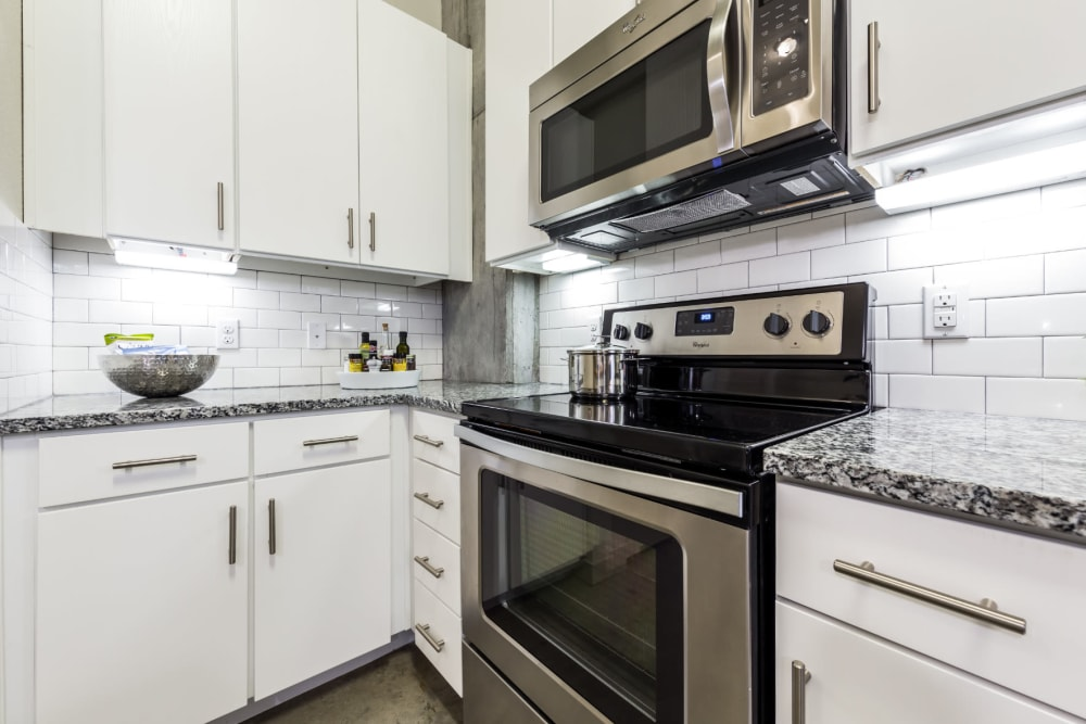 Stainless steel microwave and oven with granite countertop and tile backsplash at Marq on Burnet in Austin, Texas