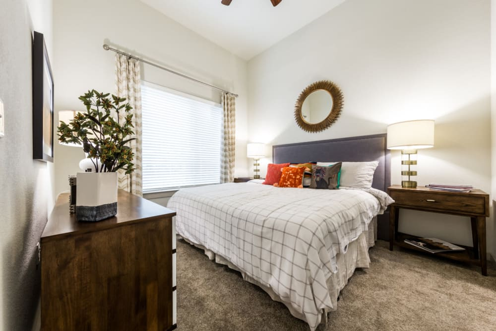 Carpeted bedroom with wood side tables, dresser, and large bed at Marq on Burnet in Austin, Texas